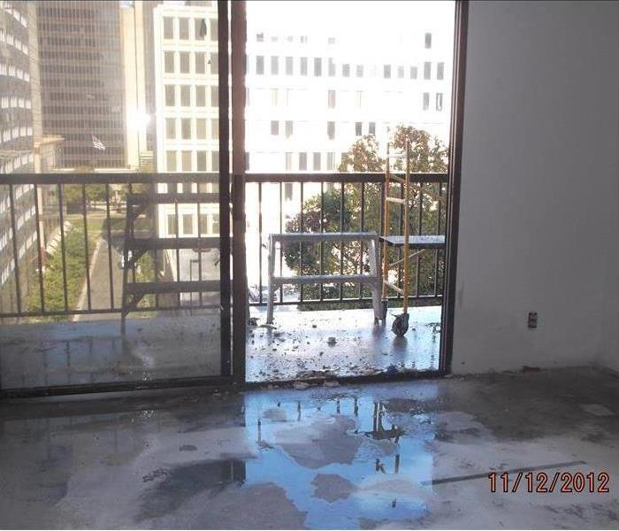 Wet flooring in apartment building, shows view out to balcony