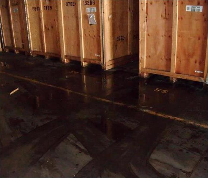 Photo of storage facility with wet flooring and wood storage containers