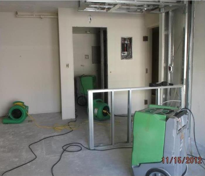 Grey floored apartment building with SERVPRO drying equipment in it