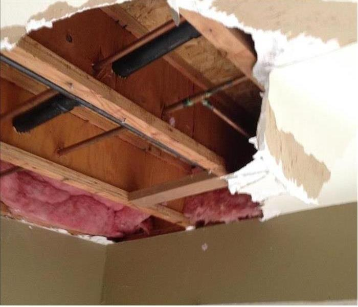 Ceiling with pieces missing exposing insulation and wood beams
